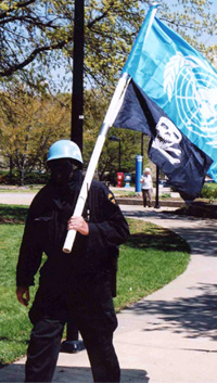 An unidentified man carries the United Nations flag and the skull and crossbones on campus Sunday during a protest against the UN flag flying at USI.